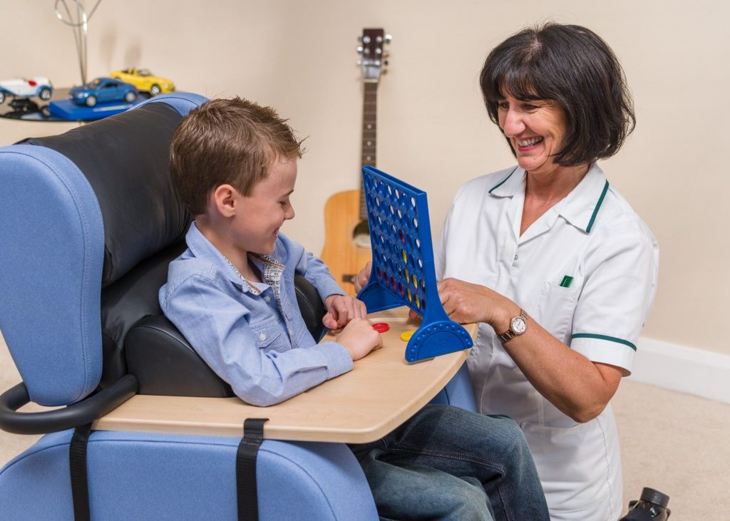 Carer playing a board game with child in a special chair